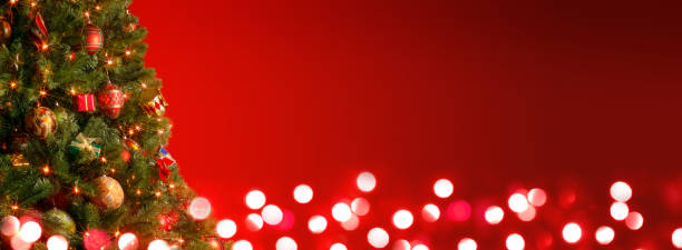 Christmas Tree In Front Of Red Background And Blurred Lights stock photo