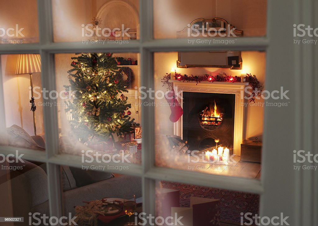 Christmas tree in living room behind window stock photo
