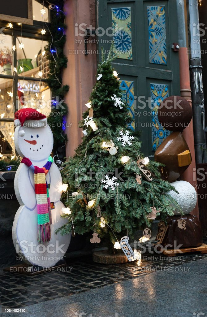 Christmas tree in pot and white Snowman near house - Royalty-free Advent Stock Photo