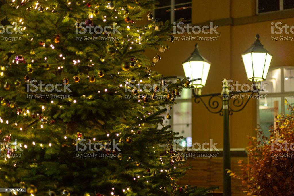 christmas tree lights at market place in advent december blue hour...