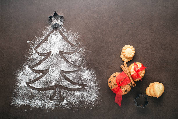 Christmas tree made from flour on a dark table, kitchen utensils and cookies stock photo