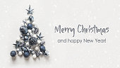 istock Christmas tree made of blue balls on grey background. Happy New Year. 1284096834