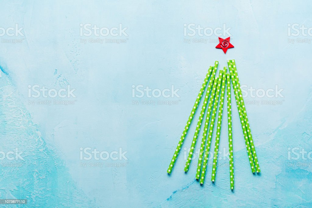 Christmas tree made of drinking colorful paper on blue background. New year concept. stock photo