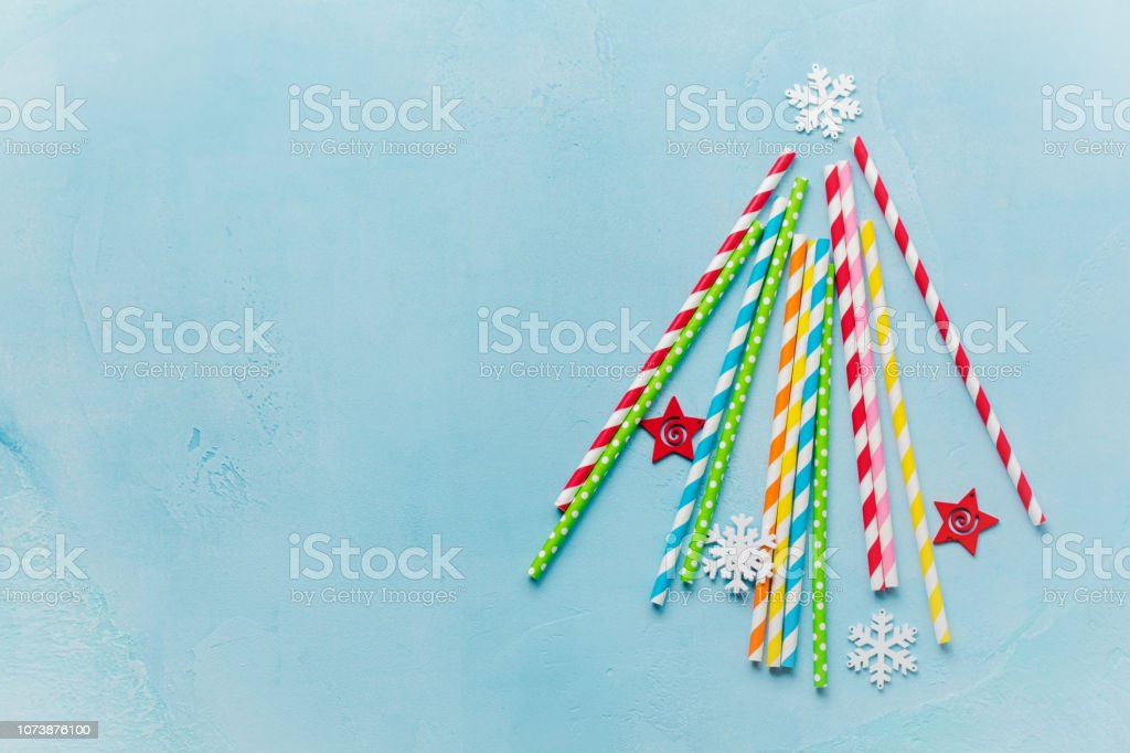 Christmas tree made of drinking colorful paper with white marshmallows and snowflakes toys on blue background. New year concept. stock photo