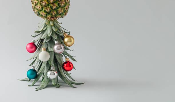 weihnachtsbaum gemacht von ananas und weihnachten christbaumkugel-dekoration. ferienkonzept. - weihnachtsessen ideen stock-fotos und bilder