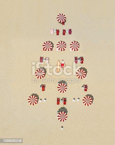 Christmas tree made of sun umbrellas in sand, Santa Claus is sunbathing.
