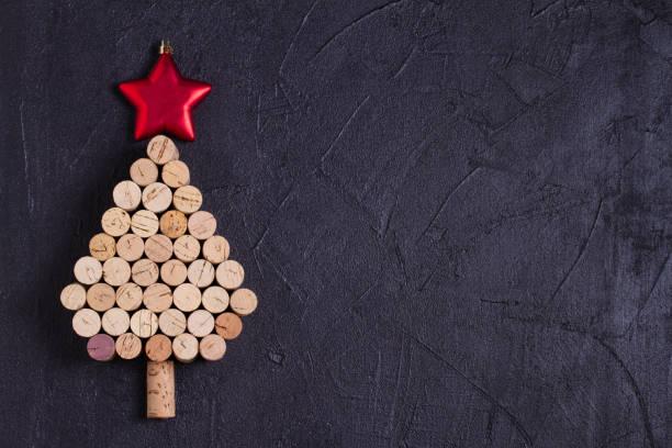 Arbol de Navidad hecho de corchos de vino sobre fondo negro. Diseño, plano, plantilla. - foto de stock