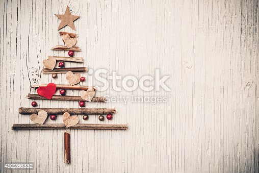 527392693 istock photo Christmas tree made of wooden branches and heart 492286332