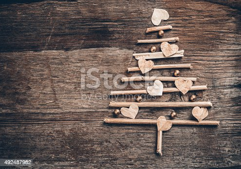 527392693 istock photo Christmas tree made of wooden branches and heart 492487982