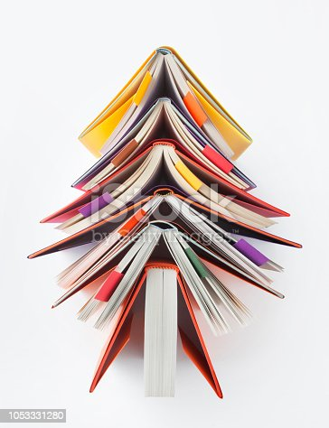 Christmas tree made out of books on white background.