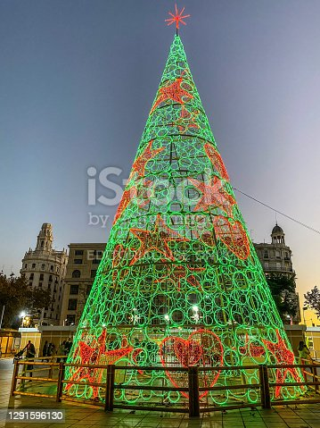Valencia, Spain - December 15, 2020: Beautiful representation of a Christmas tree made with green and red lights in the Town Hall Plaza. During this holiday period the city government decorates different parts of the city for the occasion