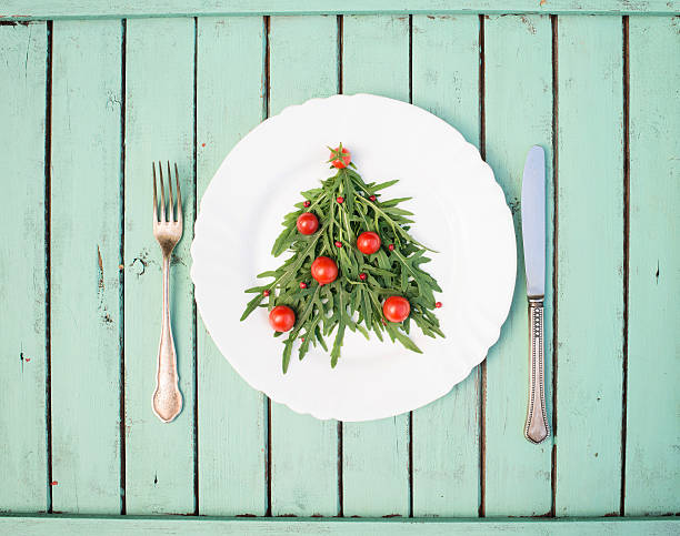 Christmas tree of arugula and cherry tomatoes on white plate. – Foto