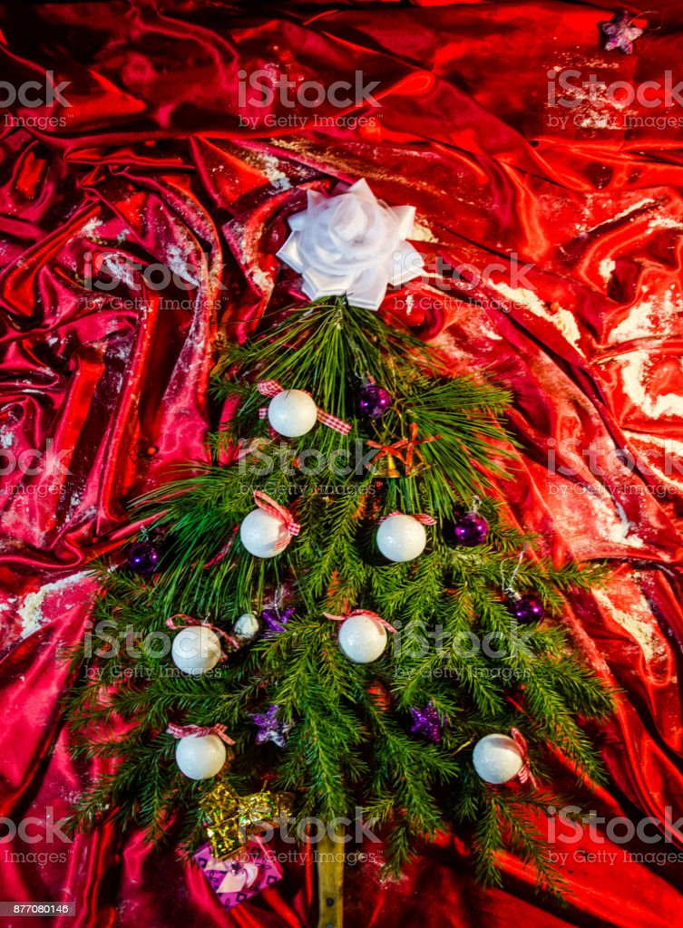 Christmas tree on a red background of silk with a garland and toys with white balls and stars of pine cones top view stock photo