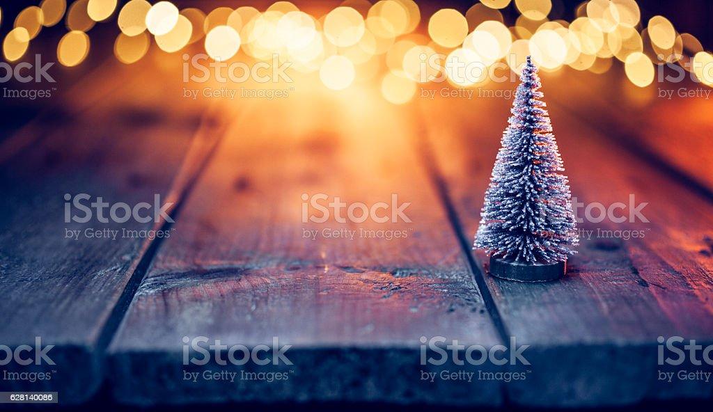 Christmas tree on old wood and defocused blue gold lights