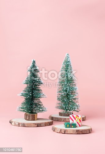 istock Christmas tree on wood log slice with present box on pastel pink studio background.Holiday festive celebration greeting card with copy space for display of design or content. 1010461750