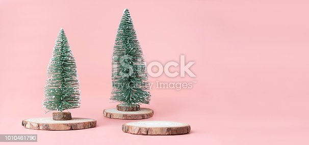 istock Christmas tree on wood log slice with present box on pastel pink studio background.Holiday festive celebration greeting card with copy space for display of design or content. 1010461790