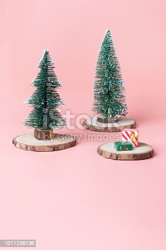 istock Christmas tree on wood log slice with present box on pastel pink studio background.Holiday festive celebration greeting card with copy space for display of design or content. 1011236136