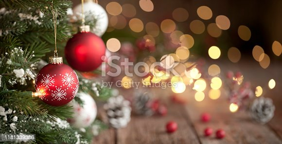 Christmas tree with red and white baubles and lights against an old wood background