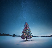 Holiday background with illuminated Christmas tree under starry night sky.