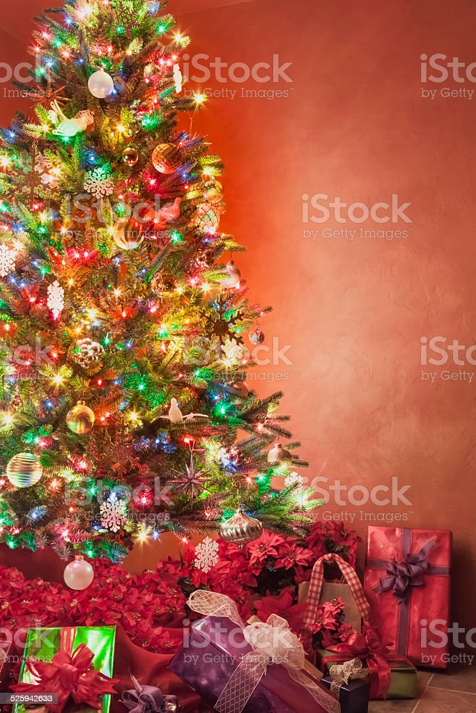 Christmas Tree Poinsettias And Gifts Against Textured Rust