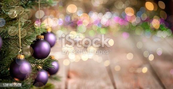 Christmas Tree, Purple Ornaments against a  Defocused Lights Background