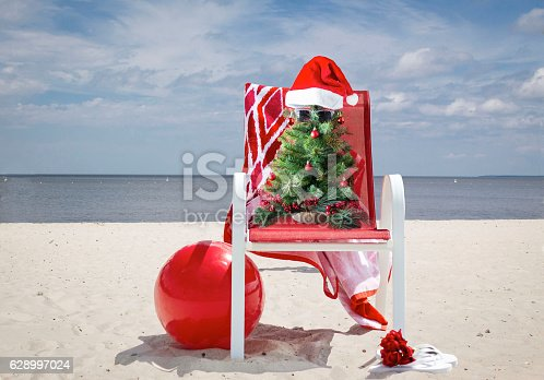 istock Christmas tree sitting in lawn chair at the beach. 628997024