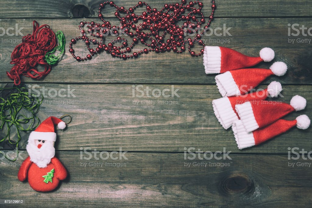 Christmas tree toys handmade. Wooden background. Top view. Making New Year decoration.  Little Santa Claus hats. stock photo