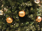 Close-up shot of Christmas tree decorated with golden-orange shiny balls and lights.