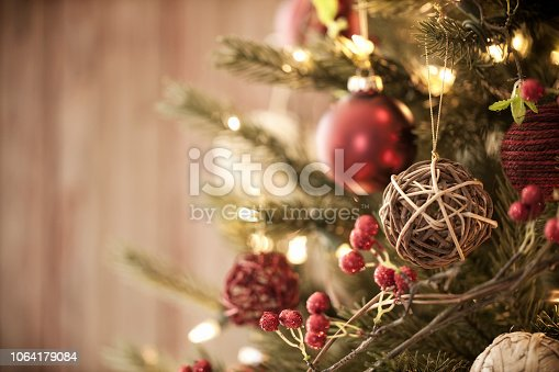 Christmas tree with eco friendly decorations, ornaments and gifts on an old wood background