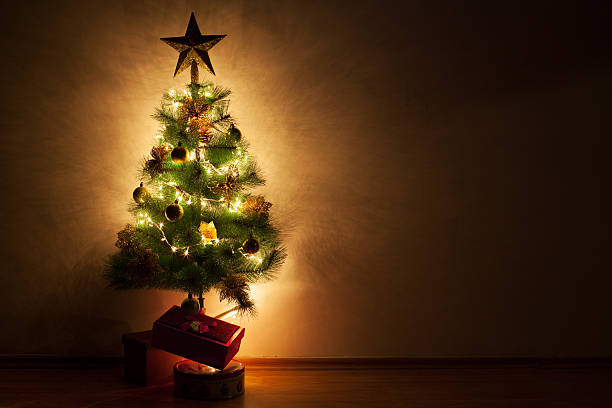 christmas tree with gifts in empty room - marko skrbic stock-fotos und bilder