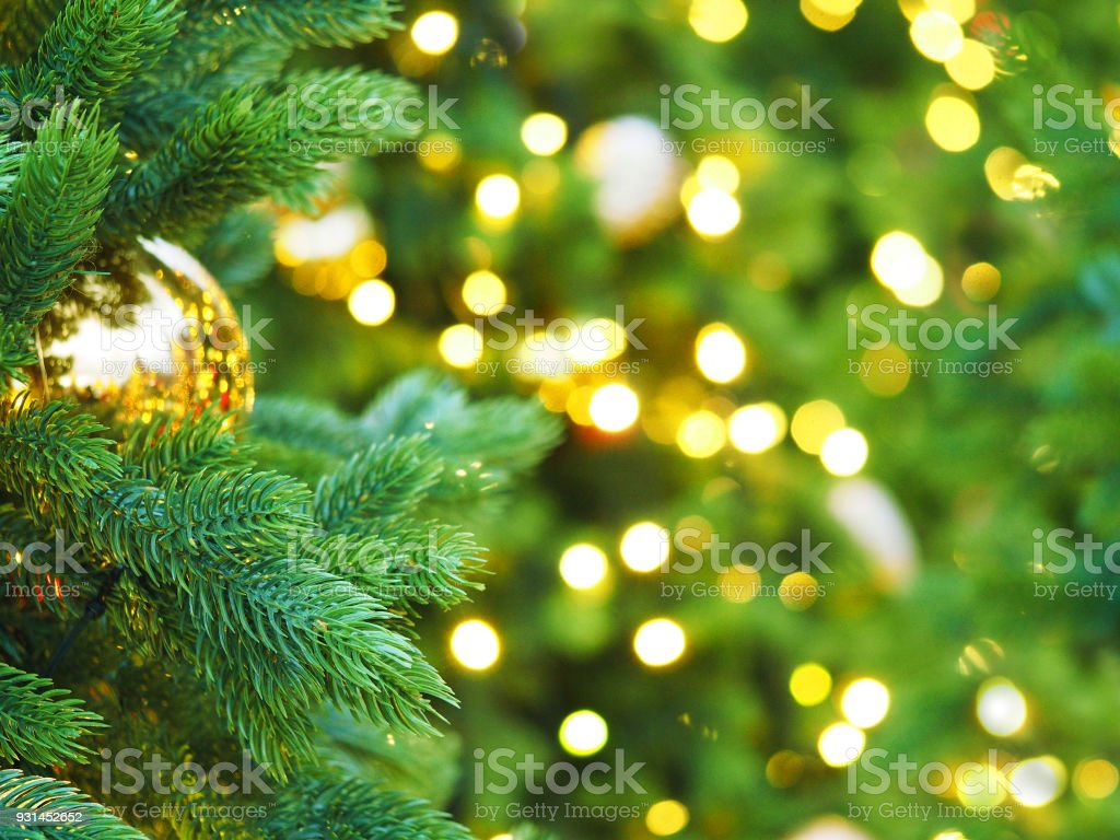 Christmas tree with holiday golden decorations and lights. Space for text. Festive New Year background, selective focus, Christmas fir tree garlands, balls and toys. Illumination stock photo