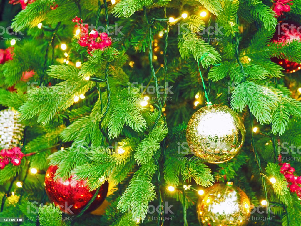 Christmas tree with holiday red and golden decorations and lights. Festive New Year background. Christmas fir tree garlands, balls, berries and toys. Illumination stock photo