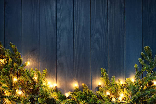 Christmas Tree With Lights On Blue Wood Background Stock Photo