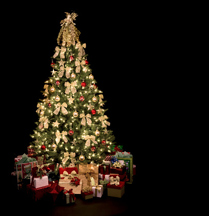 Christmas tree with nativity themed decorations, ornaments and gifts isolated on black