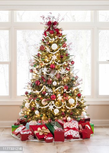 Christmas tree decorated in red, white and green with gifts against a large picture window and a wintery outdoor scene.
