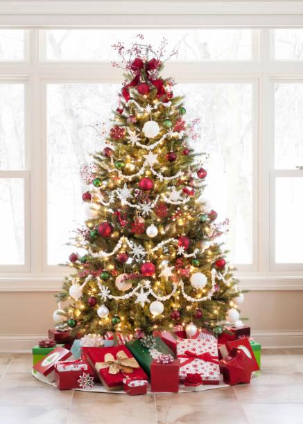 Weihnachtsbaum mit Ornamenten und Geschenken gegen ein Bildfenster – Foto