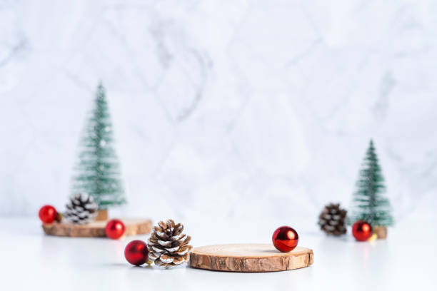 christmas tree with pine cone and decor xmas ball and empty wood log plate on white table and marble tile wall background.clean minimal simple style.holiday still life mockup to display design stock photo
