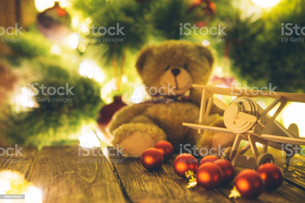Christmas tree with presents and handmade wooden airplane toys on wooden table stock photo