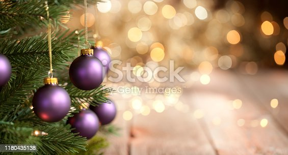 Christmas tree with purple baubles and gold lights against an old wood background