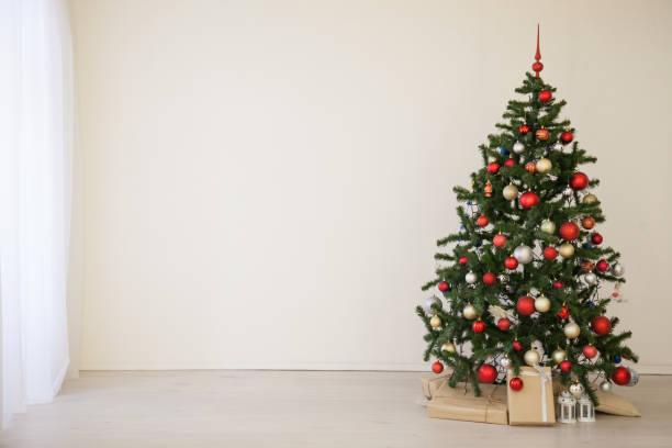 weihnachtsbaum mit roten geschenke im weißen saal weihnachten - kamin weiß stock-fotos und bilder