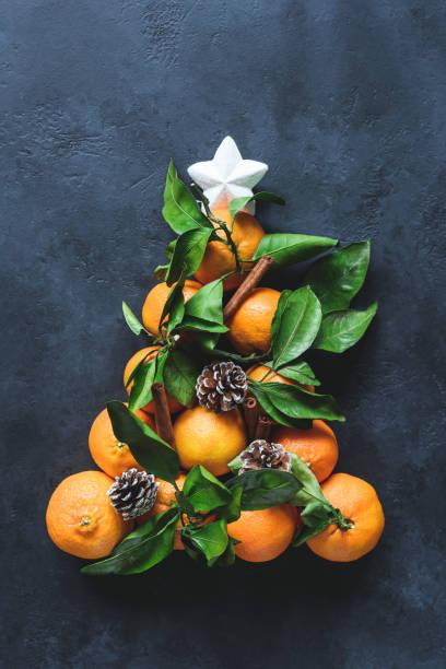 weihnachtsbaum mit mandarinen, gewürzen und tannenzapfen dekoriert mit weißen stern. - weihnachtsessen ideen stock-fotos und bilder