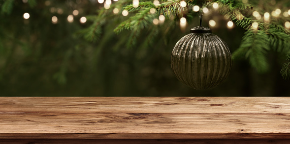 Christmas tree and golden lights with empty wooden table for a background decoration