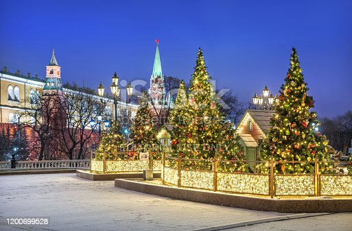 Christmas decorations on Christmas trees and houses on Manezhnaya Square in Moscow near the Kremlin on a snowy winter night