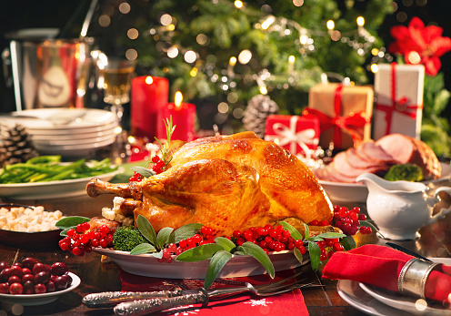 Christmas turkey dinner. Baked turkey garnished with red berries and sage leaves in front of Christmas tree and burning candles