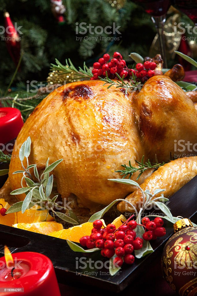 Christmas Turkey Prepared For Dinner Roasted turkey garnished with sage, rosemary, and red berries in a tray prepared for Christmas dinner. Holiday table, candles and Christmas tree with ornaments. Berry Fruit Stock Photo