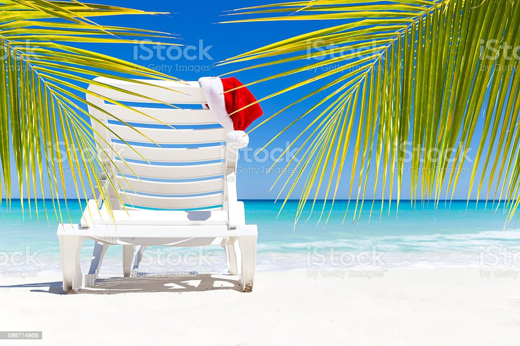 Santa Claus Hat on sunbed near tropical calm beach with turquoise...