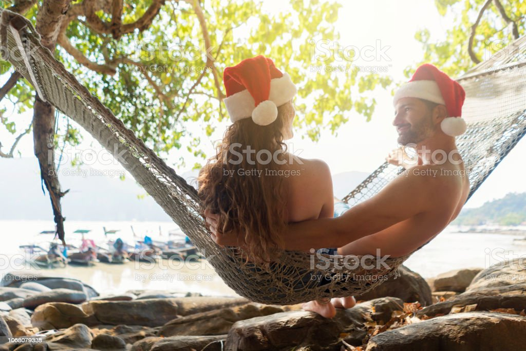 Rear view of a caucasian love couple wearing santa hats and relaxing...