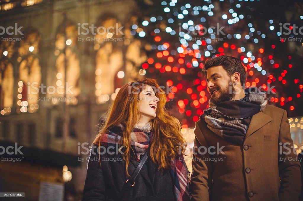 Young couple having fun outdoors at winter fair. Wearing warm...