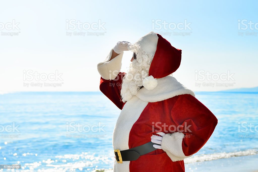 Santa is standing on the beach and he is looking for something or...