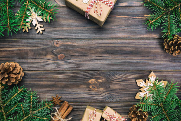 christmas vintage, toned background with fir tree and gift box on wooden table. top view with copy space for your design - christmas table imagens e fotografias de stock
